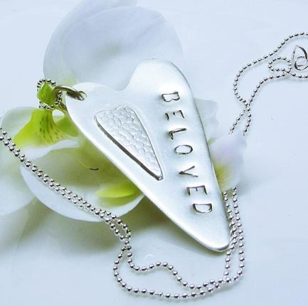 """Kimmelinessmykker: Et Håndsaget hjerte i sterling sølv har fått påmontert et mindre hjerte med teksturert overflate. På siden står det """"BELOVED"""" http://epla.no/handlaget/produkter/792866/"""